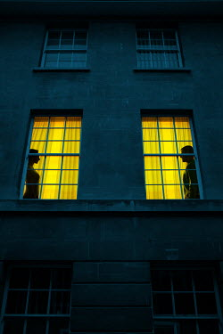 Magdalena Russocka man and woman silhouettes in windows of old townhouse at night