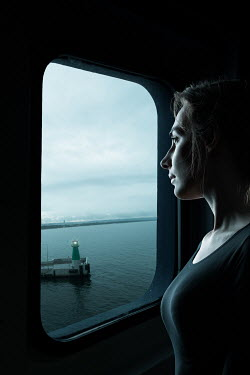 Magdalena Russocka woman at window of cruise boat looking at harbor from inside