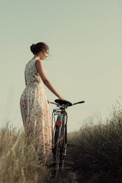 Magdalena Russocka young woman with bike standing in field