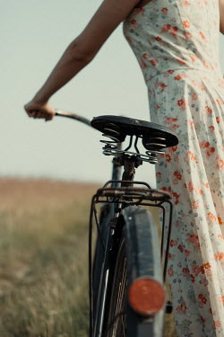 Magdalena Russocka close up of young woman with bike walking in field