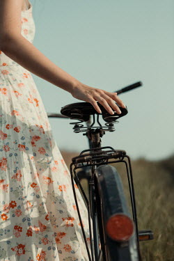 Magdalena Russocka close up of young woman with bike standing in field