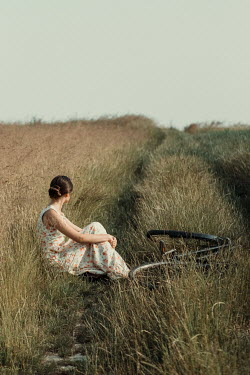 Magdalena Russocka young woman with bike sitting in field