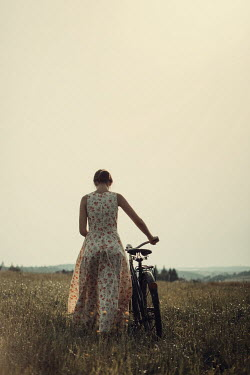 Magdalena Russocka young woman with bike walking in field