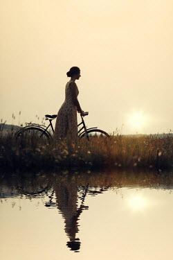 Magdalena Russocka young woman with bike standing by river