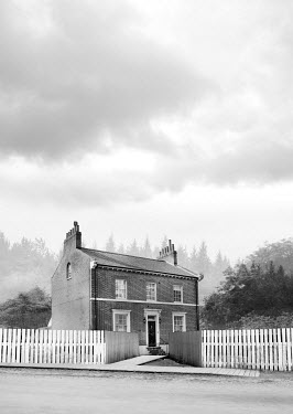 Stephen Mulcahey HISTORICAL BRICK HOUSE WITH FENCE IN COUNTRYSIDE