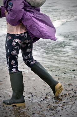 Adrian Muttitt Girl walking on beach in Dunwich, Suffolk, England