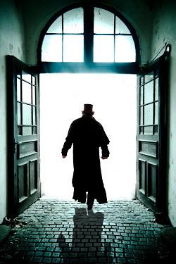 Valentino Sani Silhouette of man in top hat and coat walking through doorway