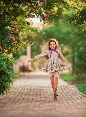 Lilia Alvarado Girl with dress and straw hat skipping on path
