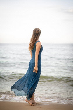 Michael Nelson Young woman in blue dress on beach