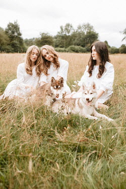Shelley Richmond Young women with husky puppies in field