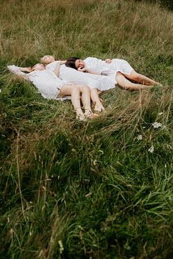 Shelley Richmond Young women in white dresses lying in field