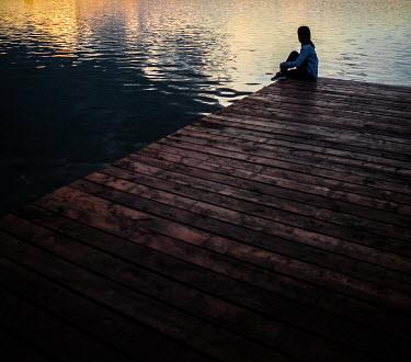 Nikaa Woman sitting on jetty at sunset
