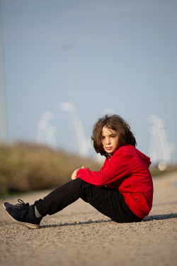 Mohamad Itani Boy in red hoodie sitting on road
