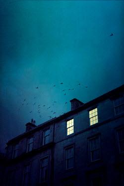 Miguel Sobreira Lit Window of Building Against Dusk Sky