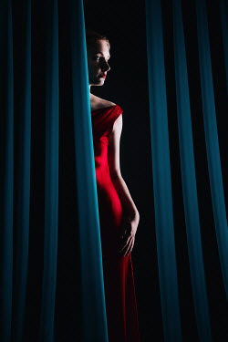 Magdalena Russocka elegant woman in red dress behind curtains