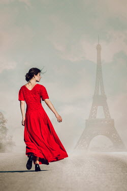 Magdalena Russocka young woman wearing red dress walking on sunlit pavement in paris