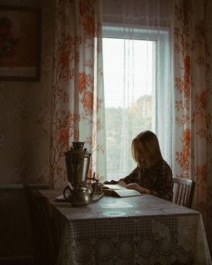 Ekaterina Pavlova Teenage girl reading at dining table