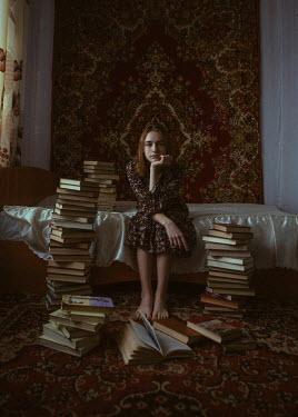Ekaterina Pavlova Teenage girl with books sitting on bed