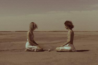 Ekaterina Pavlova Young man and woman meditating in desert