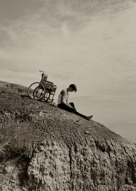Ekaterina Pavlova Young man with wheelchair sitting on hill