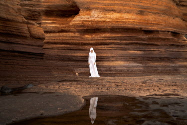 Felicia Simion WOMAN IN WHITE STANDING BY COASTAL CLIFFS