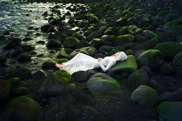 Felicia Simion WOMAN IN WHITE LYING ON ROCKS WITH SEAWEED