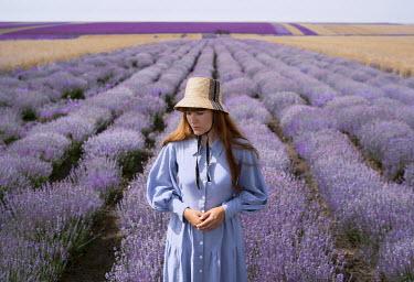Felicia Simion WOMAN IN HAT STANDING IN LAVENDER FIELD