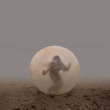 Felicia Simion WOMAN INSIDE BALL ON FOGGY BEACH
