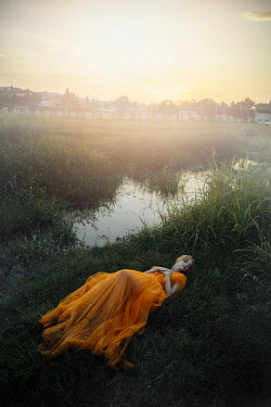 Jovana Rikalo WOMAN IN GOWN LYING BY STREAM AT SUNSET