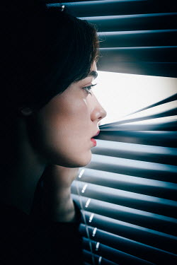 Magdalena Russocka woman peeping through blinds at night