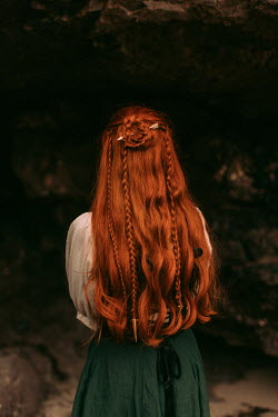 Rebecca Stice WOMAN WITH RED HAIR STANDING BY CAVE