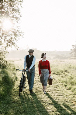 Matilda Delves 1940s young man and woman walking bicycle in field