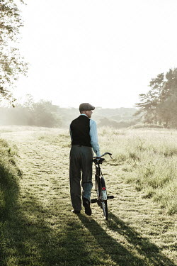 Matilda Delves 1940s young man walking bicycle in field