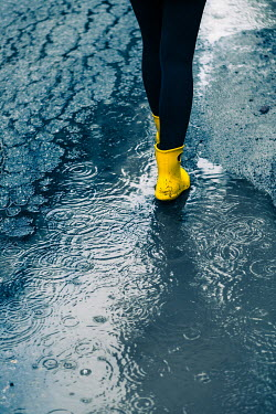 Magdalena Russocka close up of woman wearing yellow wellies walking in puddle in rain