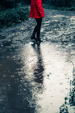 Magdalena Russocka woman wearing red jacket walking by puddle in rain