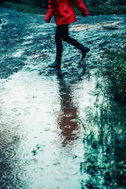 Magdalena Russocka woman wearing red jacket running by puddle in rain