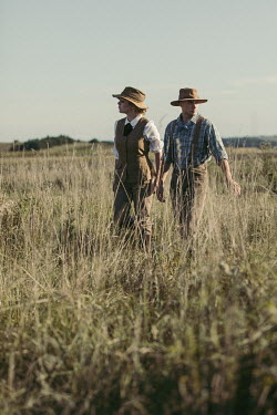 Magdalena Russocka vintage couple wearing safari outfits walking in field