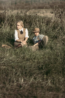 Magdalena Russocka vintage couple wearing safari outfits sitting in meadow