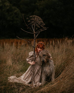 Rebecca Stice Young woman holding stick while petting dog in field