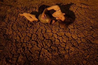 Ekaterina Pavlova WOMAN LYING WITH POT ON CRACKED EARTH