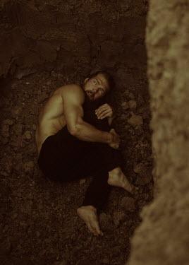 Ekaterina Pavlova BARECHESTED MAN LYING ON SOIL IN HOLE