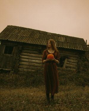 Ekaterina Pavlova Young woman holding pumpkin by abandoned house