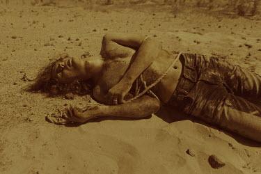 Ekaterina Pavlova Man tied in rope lying in desert