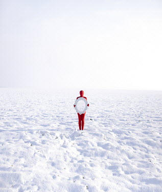 Felicia Simion Woman in red bodysuit holding mirror in snow