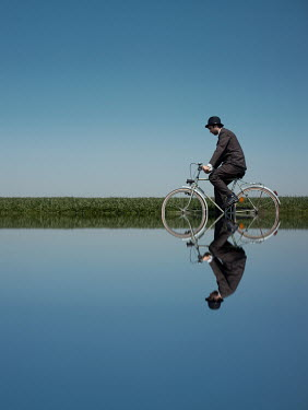 Felicia Simion Man riding bicycle in pond