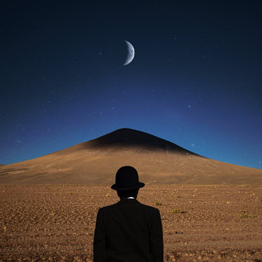 Felicia Simion Man in hat by desert mountain under crescent moon