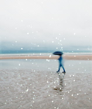 Felicia Simion Long exposure of woman with umbrella walking on beach