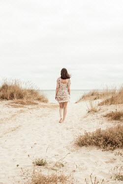 Svetlana Bekyarova Teenage girl in floral dress walking on sand dunes