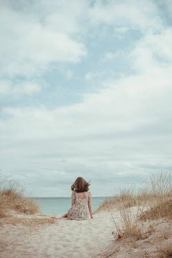 Svetlana Bekyarova Teenage girl in floral dress sitting on sand dunes