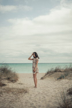 Svetlana Bekyarova Teenage girl in floral dress standing on sand dunes